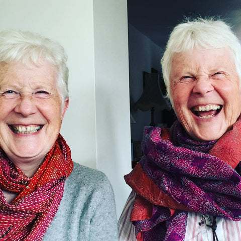 A twinning moment with two smiling ladies wearing Alleura Atelier Simply Silk scarves