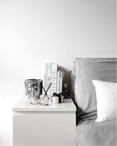 White and grey bedside with silver buddha ornament