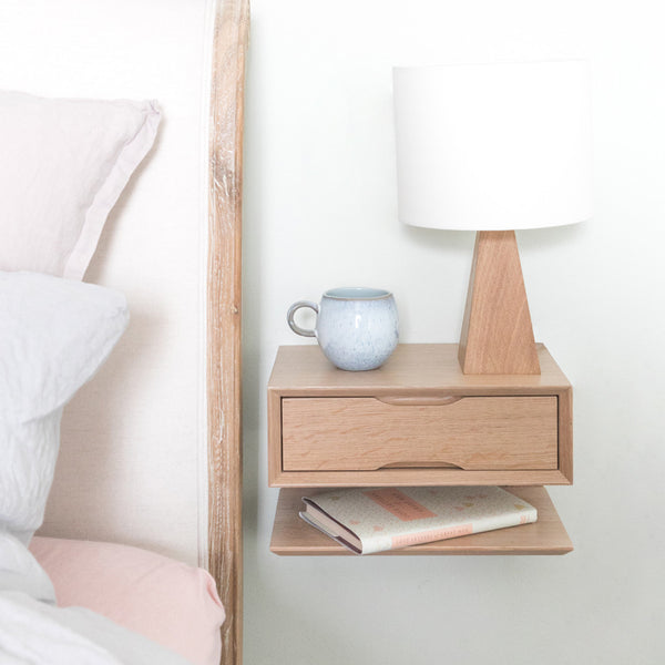 oak floating bedside table with lamp and bed