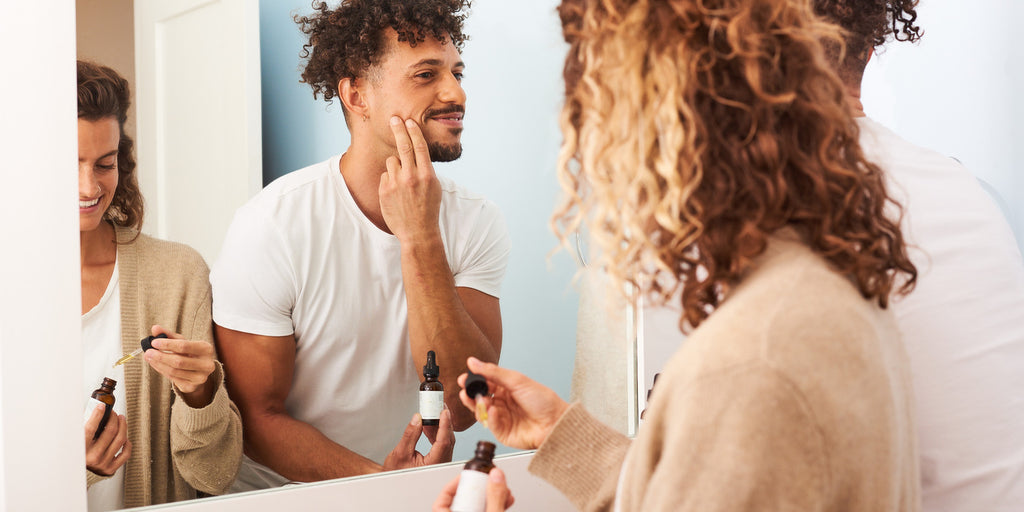 Man and woman applying OWL skincare products in mirror