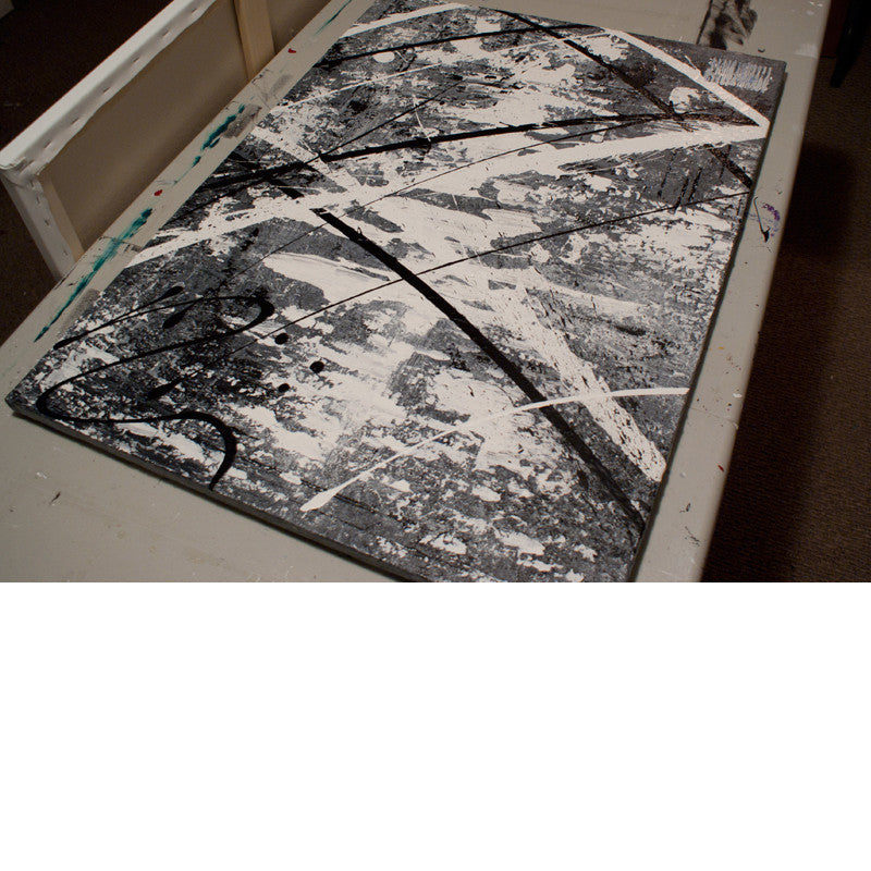 Modern decor ideas - Close up image of a grey, white and black modern abstract painting on a table