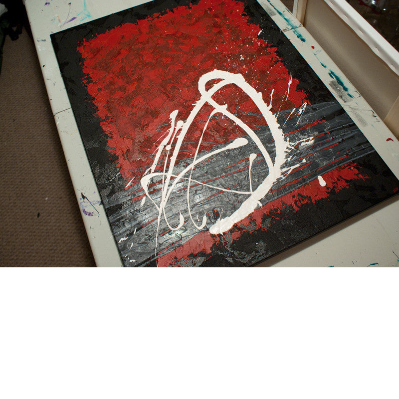 Close up image of a red, black, white and grey contemporary abstract painting on a table