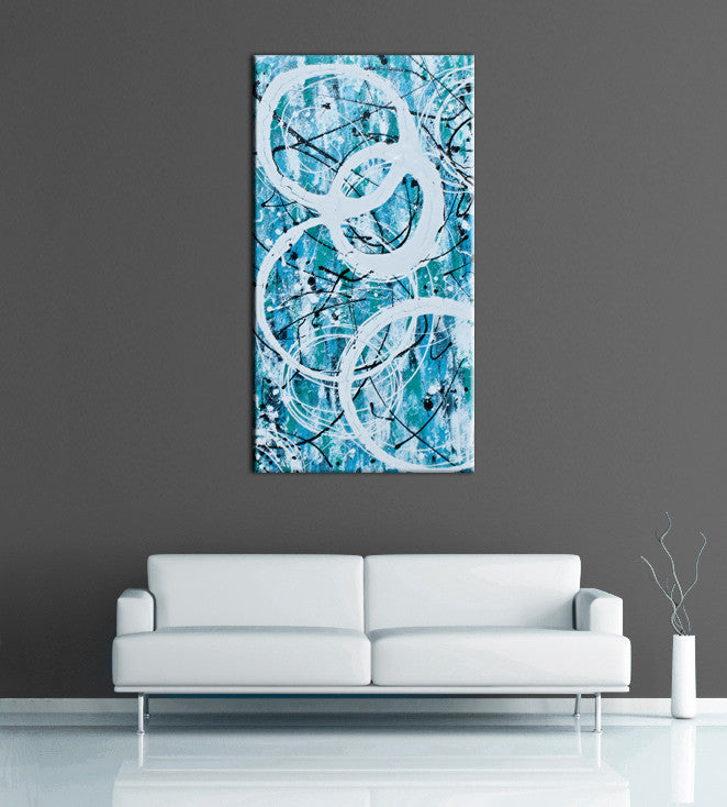 Image of a large, tall, light blue and turquoise abstract, acrylic painting featuring modern white circles. The painting is on a grey wall above a couch.