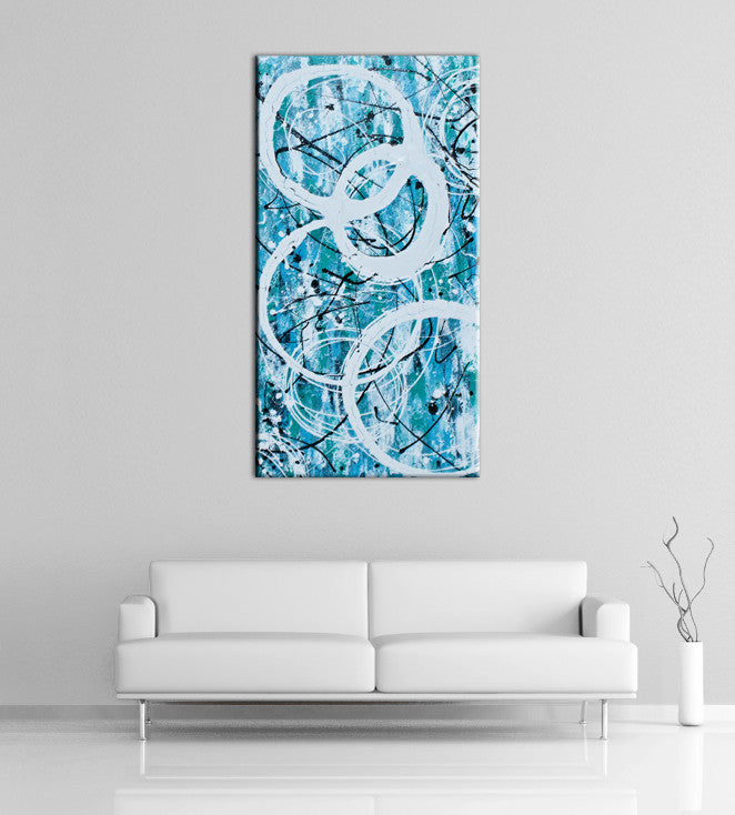 Image of a large, tall, light blue and turquoise abstract, acrylic painting featuring modern white circles. The painting is on a white wall above a couch.