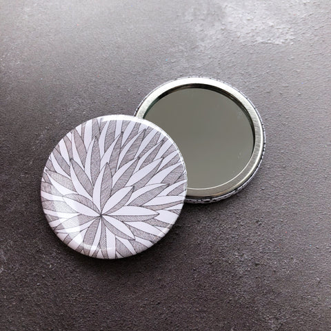 Graphic drawing of leaves on round pocket mirror