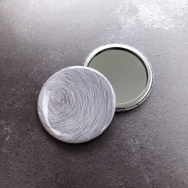 Round pocket mirror with black and white tree trunk rings illustration