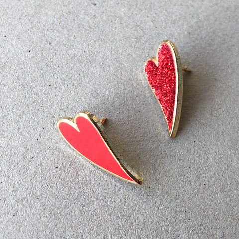 2 red heart enamel pins on grey background