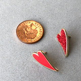 two small heart enamel pins compared to coin
