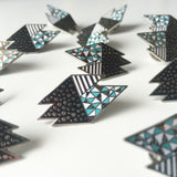 lots of geometric pin badges displayed on white surface