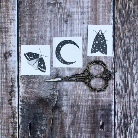 Set of 3 moth and moon temporary tattoos on wooden background