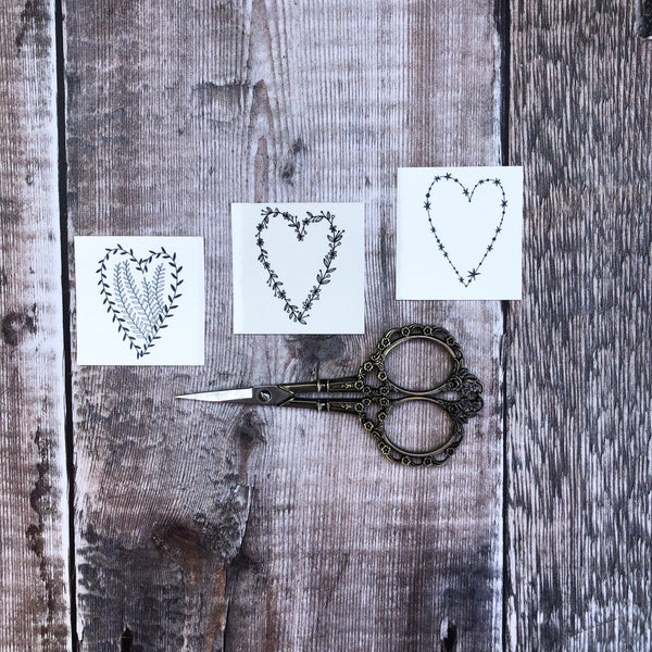 set of 3 heart temporary tattoos on wood background displayed with small scissors