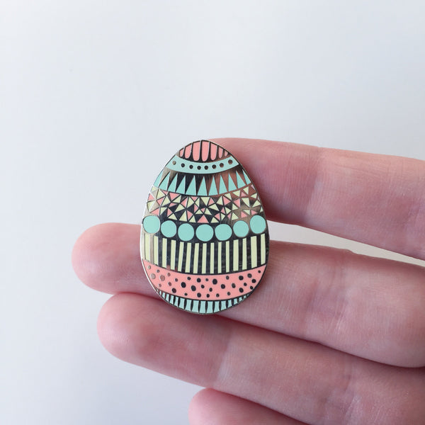 Easter egg enamel pin badge held in the hand