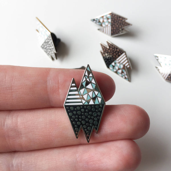 iceberg inspired enamel pin badge held in hand