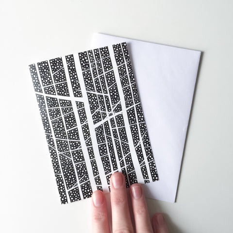Black and white trees illustration greeting card held in hand