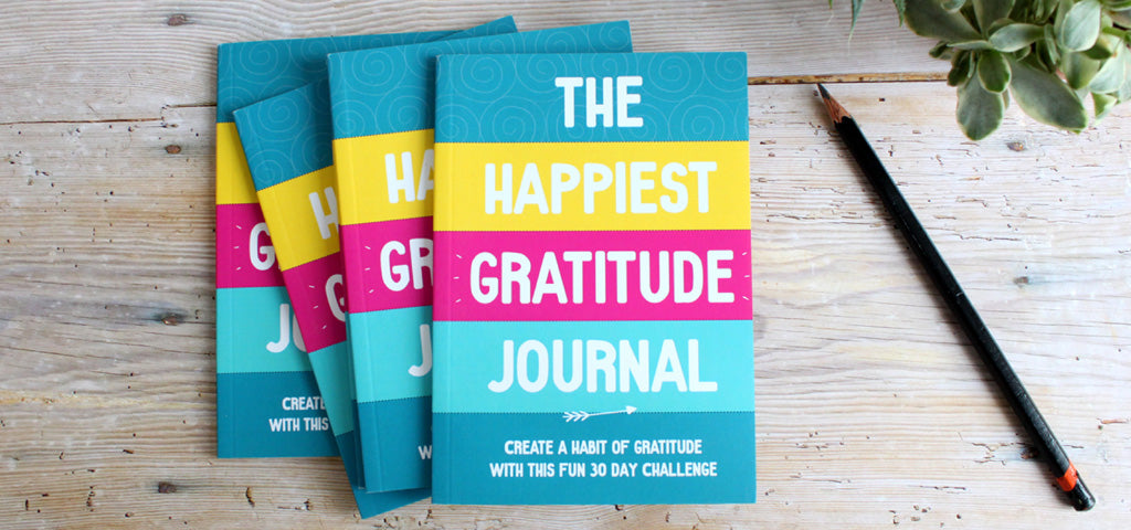 The Happiest Gratitude Journal, stack of 4 on a desk.