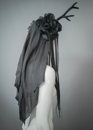 White mannequin wearing handmade black antler headdress with silk veil, flowers and braided hair falls. This handmade headdress is a regular horn of plenty, brimming with black flowers, long braids and silky textures.