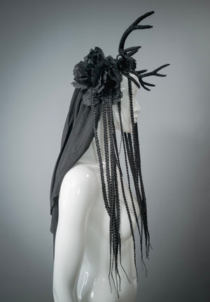 This handmade headdress is a regular horn of plenty, brimming with black flowers, long braids and silky textures.   In the back there's a long veil made of silk fabric. The braids are made of synthetic hair.  The lightweight faux horns are covered with lustrous silk fabric.