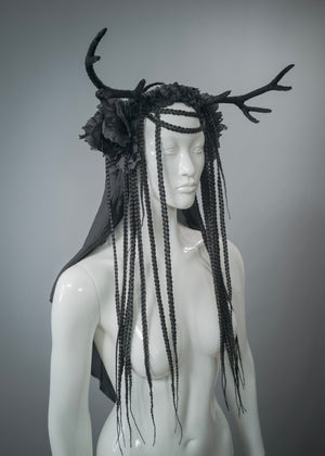 White mannequin wearing handmade black antler headdress with silk veil, flowers and braided hair falls. Unique headdress for alternative_wedding
