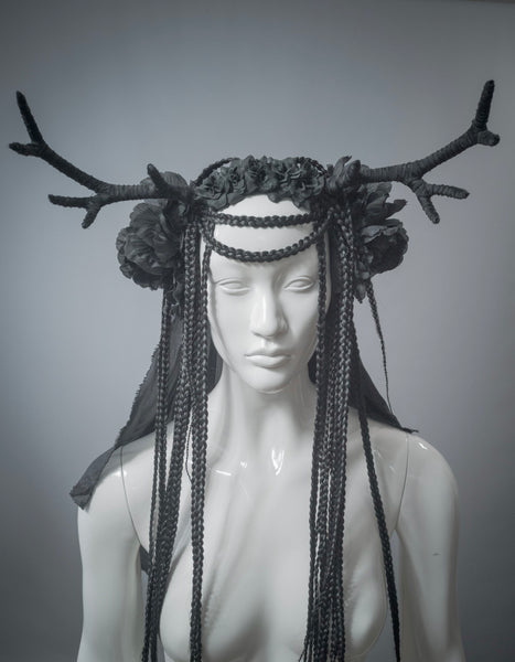 White mannequin wearing handmade black antler headdress with silk veil, flowers and braided hair falls.