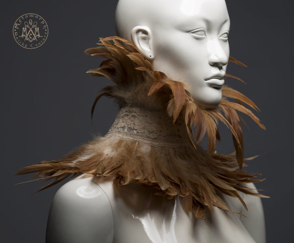 mannequin wearing a steampunk burned orange feather collar with ecru vintage lace