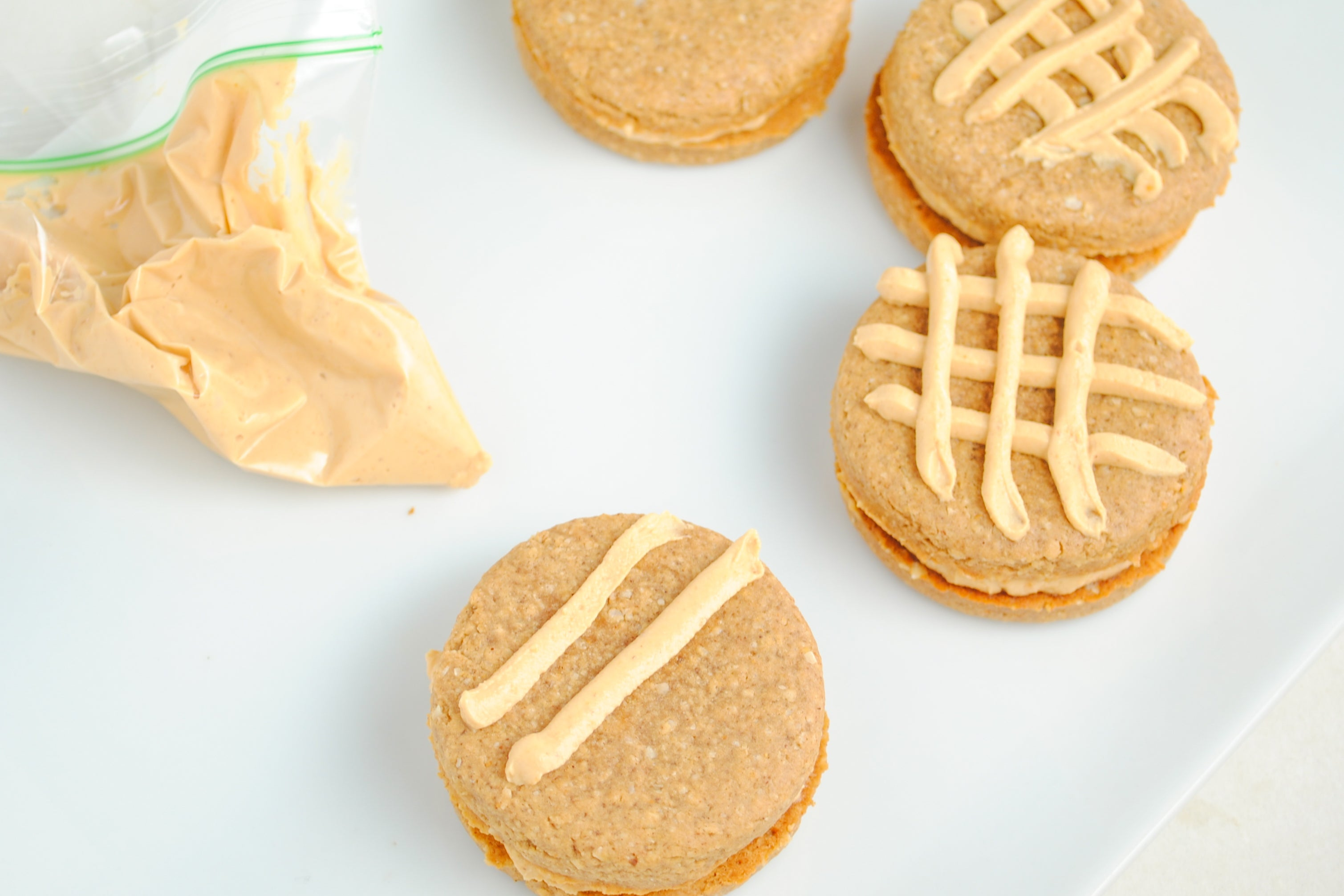 Double Peanut Butter Sandwich Cookies - pipe filling in a criss-cross on top of each sandwich cookie