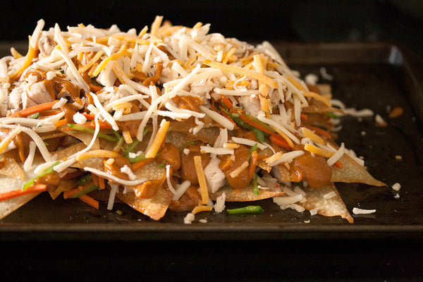 Chicken Nachos with Spicy Peanut Butter Satay Sauce - Sprinkle with half of the cooked chicken and half of the stir-fried vegetables. Drizzle with half of the peanut sauce, and then top with half of the grated cheese