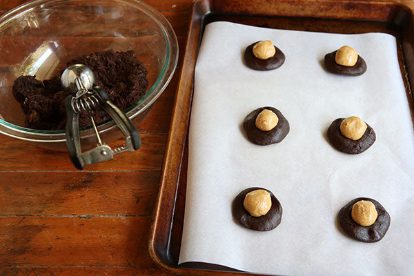 Peanut Butter Stuffed Chocolate Cookies - Take a small spoonful of the chocolate cookie dough and flatten into a disk. Place a ball of peanut butter in the center.
