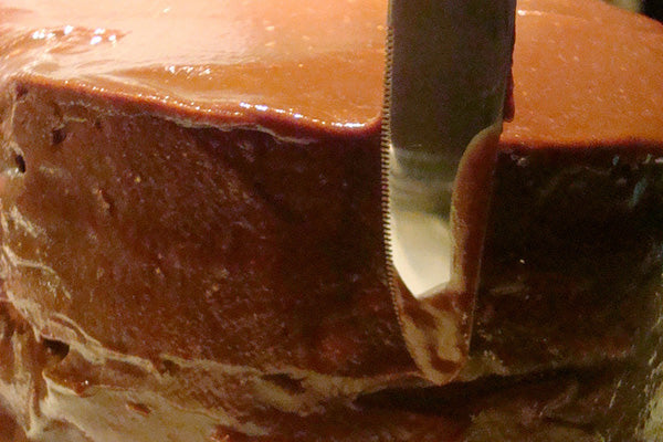"""Spoon the rest of the icing on top of the cake, bit by bit, and ice the sides of the cake by """"guiding"""" the icing from the top of the cake down the sides."""