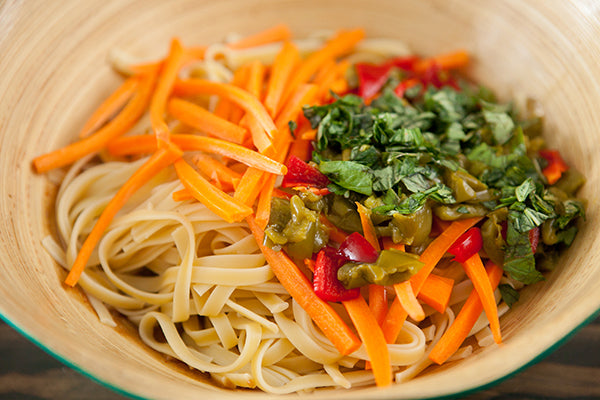 Add your fettuccini pasta, chopped peppers, carrots, and basil.  Stir well until all combined.