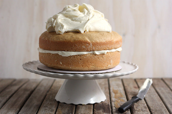 To assemble the cake, place one cooled cake round upside-down on a cake stand or plate. Cover the top with 1/2 cup of frosting. Place second cake round on top and frost entire cake with the remaining frosting.