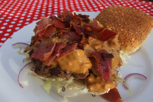 When the burgers and sauce are ready, place a little iceberg lettuce on each bun, followed by some onion, a burger, then some of the peanut butter sauce. Top with crispy bacon pieces and the top half of the bun.
