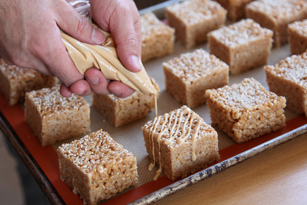 Peanut Butter Sesame Rice Crispy Treat - Then squeeze the ganache onto each rice crispy treat in a diagonal pattern.