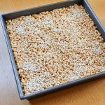 Pour the cereal into the oiled baking sheet and press down on the cereal to evenly distribute throughout the pan. Sprinkle with white or black sesame seeds and let firm up for an hour or overnight.