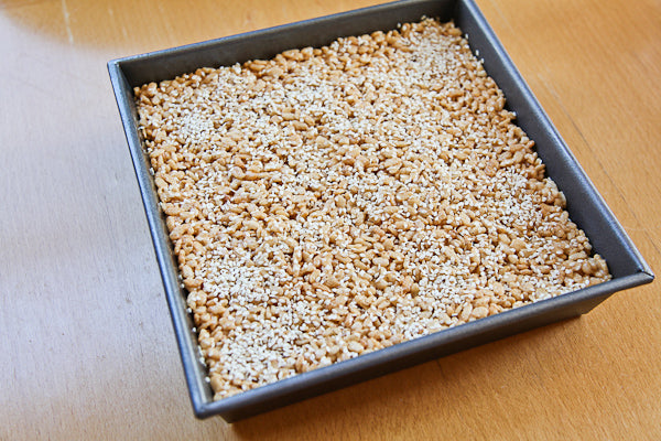 Peanut Butter Sesame Rice Crispy Treat - Pour the cereal into the oiled baking sheet and press down on the cereal to evenly distribute throughout the pan. Sprinkle with white or black sesame seeds and let firm up for an hour or overnight.