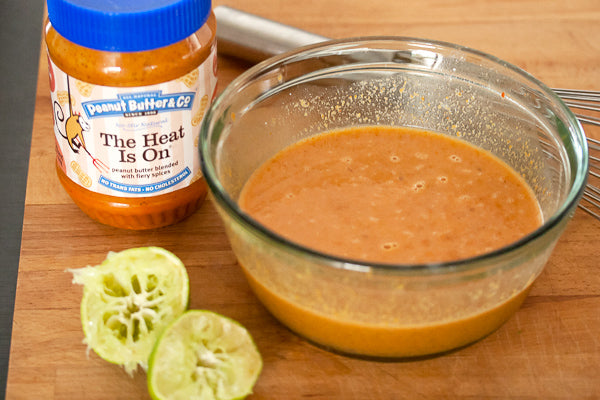 In a small mixing bowl, whisk together coconut milk, The Heat Is On peanut butter, beef broth, lime juice, brown sugar, curry paste and fish sauce until smooth and evenly combined