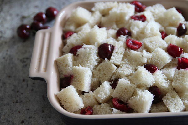 Toss the cubed bread with the pitted and halved cherries and pour into a greased 8x8 baking dish.