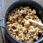 Remove the pot from heat and pour the popcorn peanut mixture into the peanut butter mixture. Stir until the popcorn is completely covered and sticky.