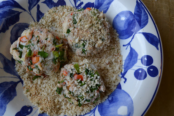 Thai-Inspired Crab Cakes with Spicy Peanut Butter Vinaigrette - Coat each crab cake with breadcrumbs