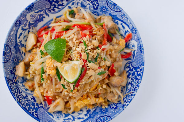 Stir Fried Noodles with Peanut Butter Sauce - Plate and top with crushed peanuts and lime wedges