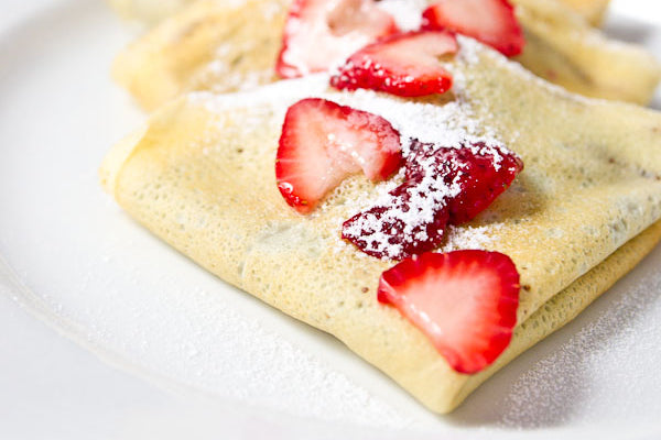 Dark Chocolate Peanut Butter and Strawberry Crepes - Plate the crepes, top with some more sliced strawberries for garnish, then sprinkle with powdered sugar