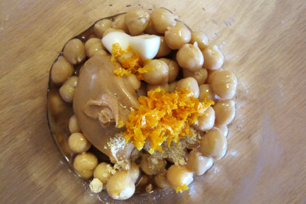 Orange-Peanut Butter Hummus - In a large bowl, place chickpeas, peanut butter, garlic chunks, ginger, soy sauce, orange juice, 1 teaspoon of the orange zest, and agave nectar