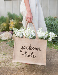 Small Jackson Hole Reusable Shopping Tote In Black Font With Flowers Inside Being Held | The Little Market