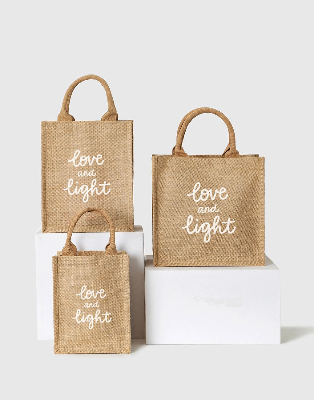 Small, Medium, And Large Love And Light Reusable Gift Totes In White Font | The Little Market