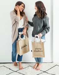 Medium Falala And Medium Merry Christmas Reusable Gift Totes In Black Font Being Modeled | The Little Market