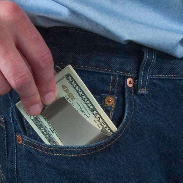 Storus® Smart Money Clip - shown bieng placed into a front pants pocket