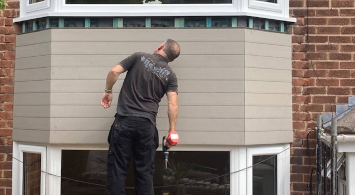 man inspecting newly installed composite cladding