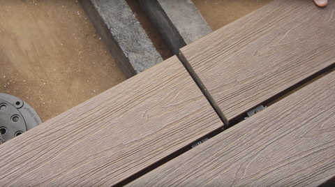 Installation of the second row of decking boards; in this case, butt joints.