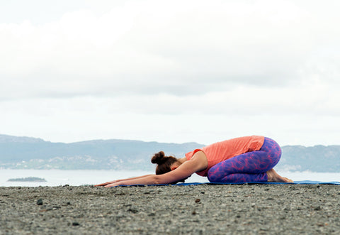 Woman Performing the Yoga Child's Pose Outside