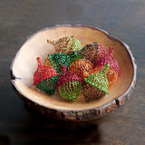 a bowl with decorative mesh acorns