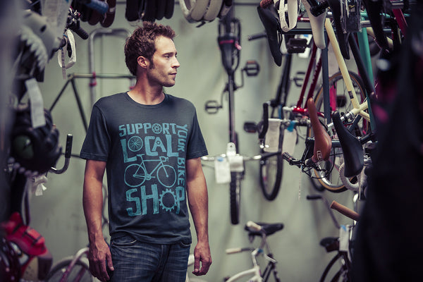 Lifestyle image of a man wearing the black Merino support your local bike shop bike t-shirt